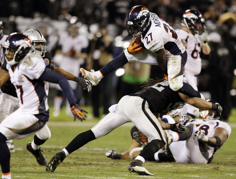 Denver Broncos running back Knowshon Moreno carries the ball and leaps over Oakland Raiders linebacker Philip Wheeler during the fourth quarter of an NFL football game in Oakland, Thursday, Dec. 6, 2012. (AP Photo/Ben Margot)