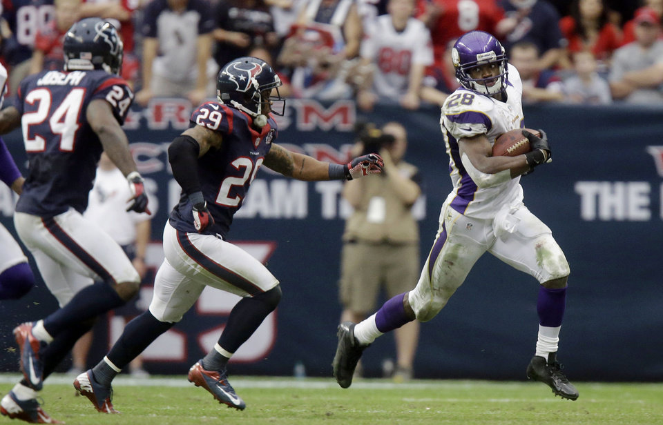 Photo - Minnesota Vikings running back Adrian Peterson (28) rushes for a gain as Houston Texans' Glover Quin (29) and Johnathan Joseph (24) defend during the third quarter of an NFL football game Sunday, Dec. 23, 2012, in Houston. (AP Photo/Patric Schneider)