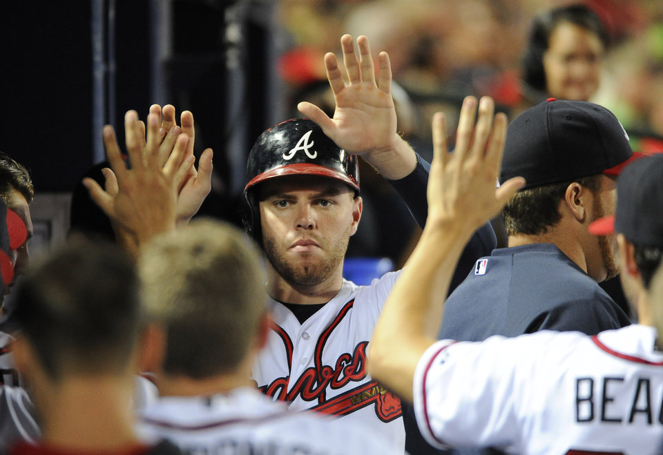 Photo - Atlanta Braves' Freddie Freeman, center, is greeted in the dugout after scoring against the San Diego Padres on a walk to Justin Upton during the eighth inning of a baseball game Friday, July 25, 2014, in Atlanta. The Padres won 5-2. (AP Photo/David Tulis)