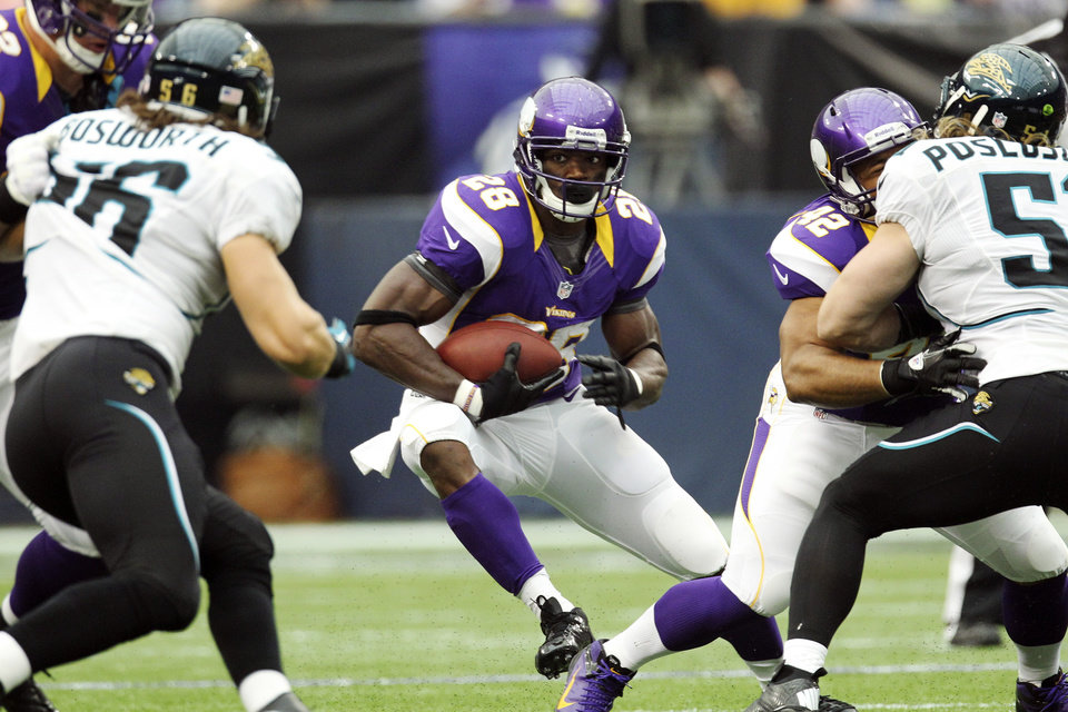 Photo -   Minnesota Vikings running back Adrian Peterson, center, runs the ball during the first half of an NFL football game against the Jacksonville Jaguars, Sunday, Sept. 9, 2012, in Minneapolis. (AP Photo/Genevieve Ross)