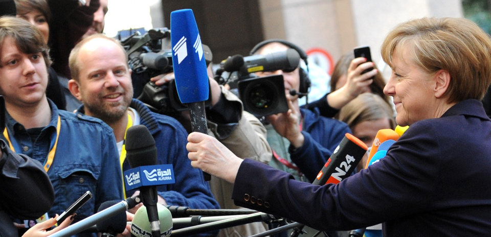 Photo - German Chancellor Angela Merkel, right, hands a microphone back to a member of the media as she arrives for an EU summit in Brussels on Thursday, March 20, 2014. The EU Commission president wants a two-day summit of European Union leaders to center on boosting the fledgling government in Kiev rather than focus exclusively on sanctions against Russia over its annexation of Ukraine's Crimea peninsula. (AP Photo/Eric Vidal)