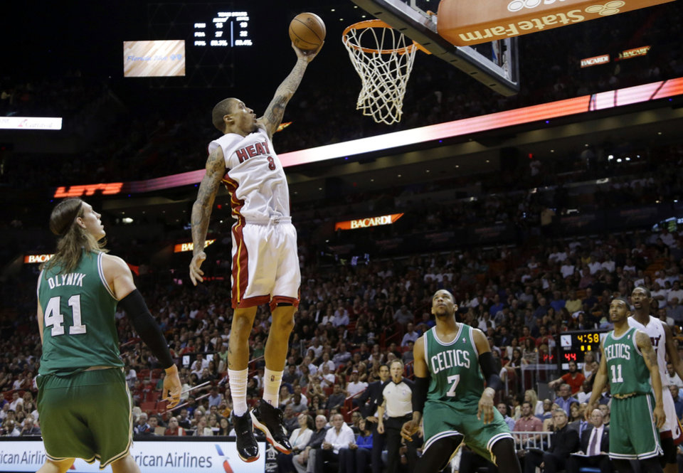 Photo - Miami Heat's Michael Beasley (8) shoots as Boston Celtics' Kelly Olynyk (41), Jared Sullinger (7) and Courtney Lee (11) stand by during the first half of an NBA basketball game Saturday, Nov. 9, 2013, in Miami. (AP Photo/Lynne Sladky)