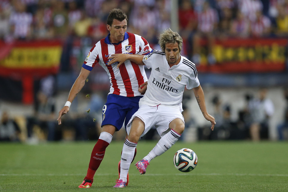 Photo - Real Madrid Fabio Coentrao from Portugal, right, duels for the ball with Atletico Madrid's Mario Mandzukic from Croatia during a Spanish Super Cup soccer match at the Vicente Calderon stadium in Madrid, Spain, Friday, Aug. 22, 2014 . (AP Photo/Daniel Ochoa de Olza)