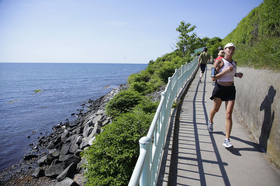 Photo - A runner and walkers travel along the Newport Cliff Walk Tuesday, June 24, 2014 in Newport, RI. Parts of the well known attraction were damaged by Superstorm Sandy in 2012 and official reopened in a ribbon cutting ceremony.  The storm washed away and damaged several sections of the walk, and most of it has been closed since the 2012 storm.  (AP Photo Stephan Savoia)