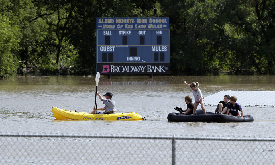 Photo - A kayaker pulls a raft with children around a flooded baseball park in San Antonio, Saturday, May 25, 2013, in San Antonio. San Antonio International Airport recorded more than nine inches of rain since midnight. (AP Photo/Eric Gay)