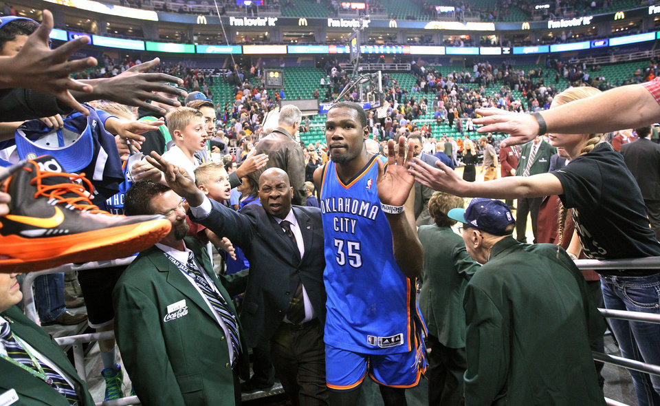 Photo -  Fans reach for Oklahoma City Thunder's Kevin Durant (35) following an NBA basketball game against the Utah Jazz, Wednesday, Oct. 30, 2013, in Salt Lake City. The Thunder won 101-98. (AP Photo/Rick Bowmer)