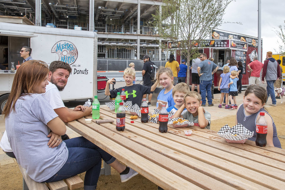 Photo - A family enjoys lunch during the grand opening weekend of Scissortail Park in Oklahoma City, Sunday, Sept. 29, 2019. (Alonzo Adams for The Oklahoman)