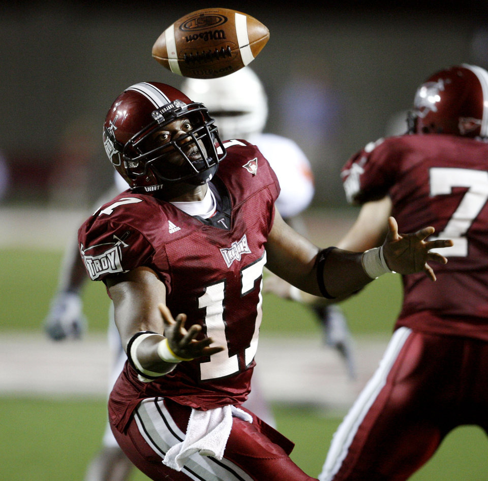 Photo - Omar Haugabook jugles a snap in second half action during the college football game between the Troy University Trojans and the Oklahoma State University Cowboys at Movie Gallery Veterans Stadium in Troy, Ala., Friday, September 14, 2007. BY STEVE SISNEY, THE OKLAHOMAN