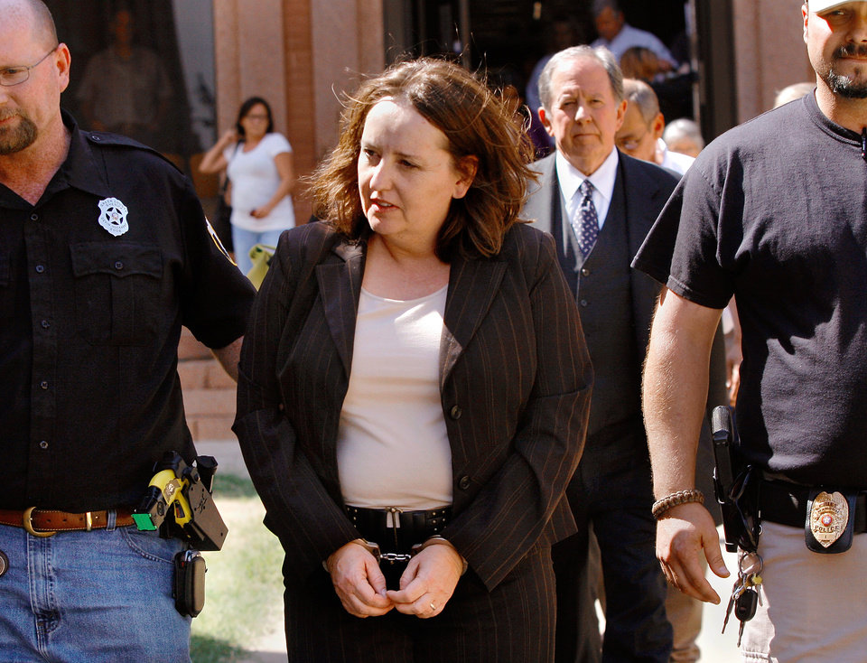 Bobbi Parker is taken in handcuffs to the Greer County jail after being found guilty Wednesday afternoon. Walking behind her is her attorney, Garvin Isaacs. At left is Greer County Sheriff Devin Huckabay. At right is Mangum Police Chief Bray Woodress. Jurors returned a guilty verdict and recommended a one-year sentence to punish Bobbi Parker on a charge of aiding prison inmate Randolph Dial escape from the Oklahoma State Reformatory in 1994. Dial died in 2007. The verdict was given about 2:30 Wednesday afternoon, Sep. 21, 2011. Photo by Jim Beckel, The Oklahoman
