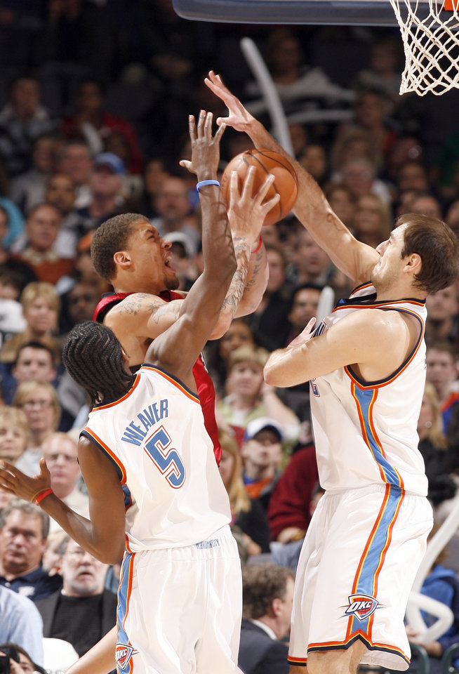 Photo - Oklahoma City's Kyle Weaver (5) and Nenad Krstic (12) defend Miami's Michael Beasley during the NBA game between the Oklahoma City Thunder and the Miami Heat Sunday Jan. 18, 2009, at the Ford Center in Oklahoma City. PHOTO BY SARAH PHIPPS, THE OKLAHOMAN