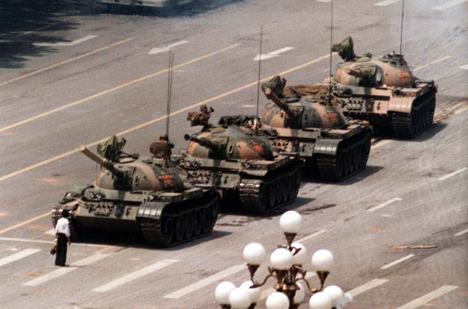 Photo - FILE - In this June 5, 1989 file photo, a Chinese protestor blocks a line of tanks heading east on Beijing's Cangan Blvd. June 5, 1989 in front of the Beijing Hotel. The man, calling for an end to the violence and bloodshed against pro-democracy demonstrators, was pulled away by bystanders, and the tanks continued on their way. Thursday June 4, 2009 marks the 20th anniversary of the Chinese military assault on demonstrators on the night of June 3-4, 1989 in Tiananmen Square. (AP Photo/Jeff Widener, File) ORG XMIT: NY112