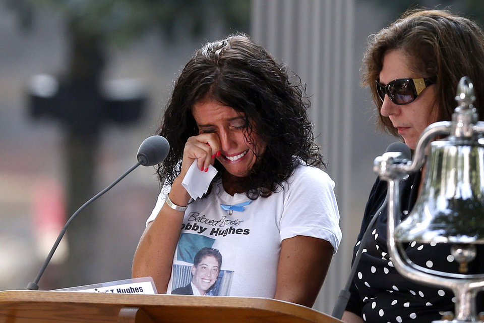 Photo - A woman wipes her eyes after reading the name of her brother, Bobby Hughes, as friends and relatives of the victims of the 9/11 terrorist attacks gather at the National September 11 Memorial at the World Trade Center site, Wednesday, Sept. 11, 2013, for a ceremony marking the 12th anniversary of the attacks in New York. (AP Photo/Jason DeCrow)