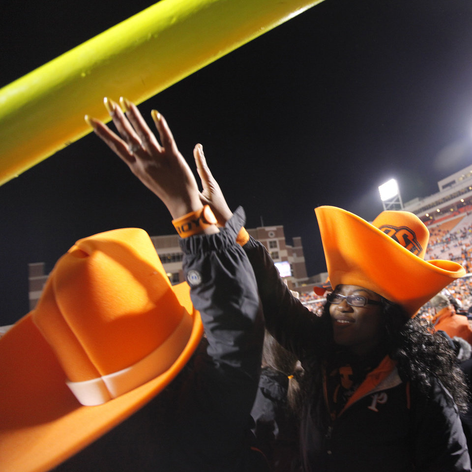 Photo - Cowboy fans reach to touch the goal post that was tore down after OSU's 44-10 win over Oklahoma during the Bedlam college football game between the Oklahoma State University Cowboys (OSU) and the University of Oklahoma Sooners (OU) at Boone Pickens Stadium in Stillwater, Okla., Saturday, Dec. 3, 2011. Photo by Chris Landsberger, The Oklahoman