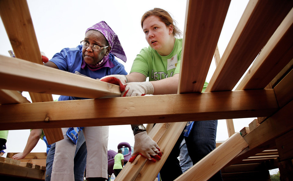 Photo - Marie Hopkins, left, and Tara Simmons place wooden planks on top of boards as they make a platform on the playground. Organizers said about 140 volunteers from Partners in Public Health, Blue Cross and Blue Shield of Oklahoma, organizers from KaBOOM! and residents of the Oklahoma City community will provided the labor on Saturday, June 8, 2013, to build a new playground at the Northeast Regional Health and Wellness Center on NE 63 Street, east of MLK Blvd.  The new playground's design is based on drawings created by children who participated in a Design Day event in April.   Photo  by Jim Beckel, The Oklahoman.