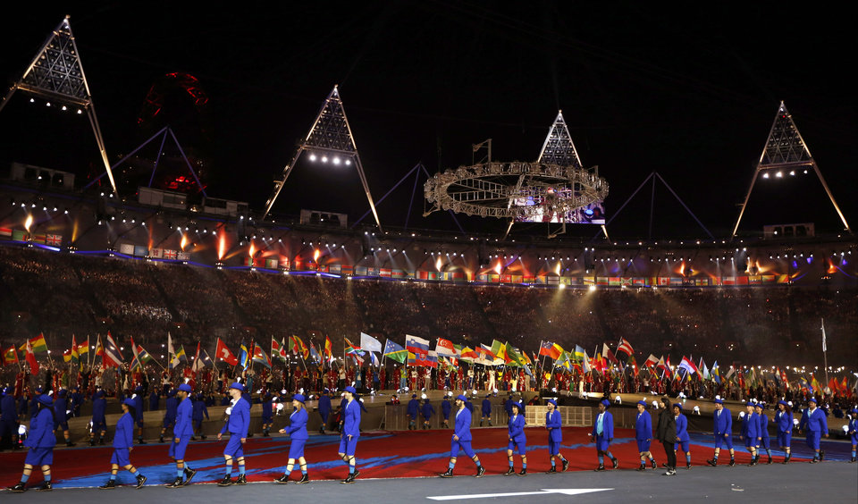 Photo -   Flag bearers parade in the background as performers walk in the foreground during the Closing Ceremony at the 2012 Summer Olympics, Sunday, Aug. 12, 2012, in London. (AP Photo/Matt Dunham)