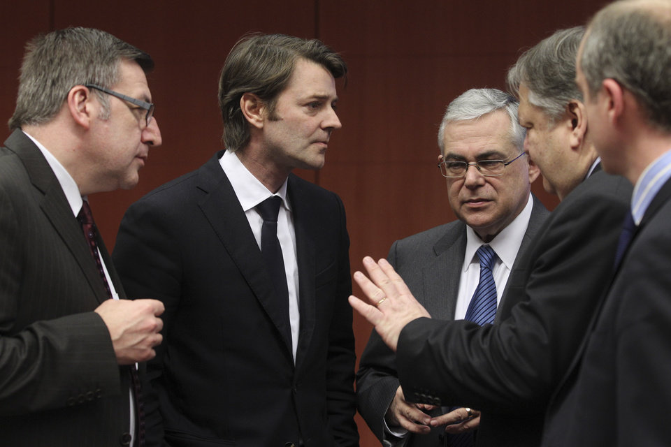 Photo -   Greek Finance Minister Evangelos Venizelos, second right, speaks with from left, Belgium's Finance Minister Steven Vanackere, French Finance Minister Francois Baroin and Greek Prime Minister Lucas Papademos during a round table meeting of eurozone finance ministers at the EU Council building in Brussels on Monday, Feb. 20, 2012. Eurozone governments will likely approve on Monday a long-elusive rescue package for Greece, saving it from a potentially calamitous bankruptcy next month, senior officials said. But finance ministers meeting in Brussels will have a few last issues to wrangle over, such as tighter controls over Greece's spending and further cuts to the country's debt load. (AP Photo/Yves Logghe)