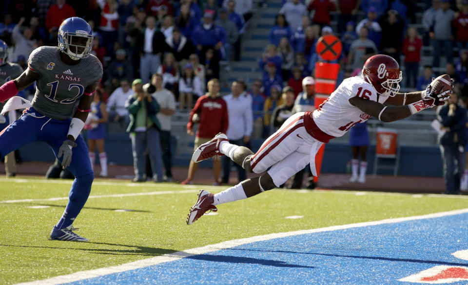 Photo - OU's Jaz Reynolds (16) leaps for a touchdown in front of KU's Dexter McDonald (12) during the college football game between the University of Oklahoma Sooners (OU) and the University of Kansas Jayhawks (KU) at Memorial Stadium in Lawrence, Kan., Saturday, Oct. 19, 2013. Photo by Bryan Terry, The Oklahoman