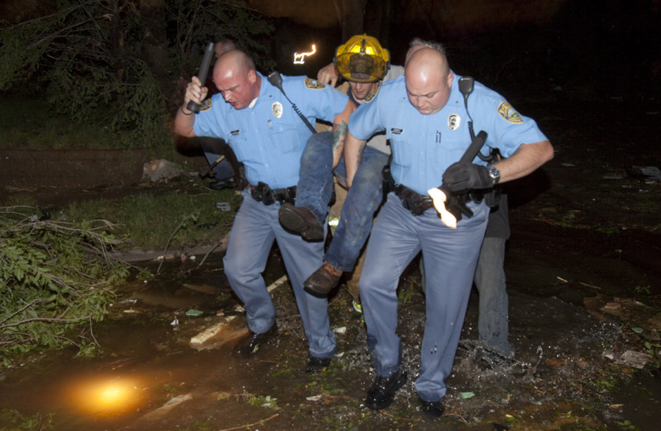 Photo -   Sheriff's deputies carry out an injured man from a south Wichita neighborhood after a tornado caused massive destruction in Wichita, Kansas on Saturday night April 14, 2012. Tornadoes were spotted across the Midwest and Plains on Saturday as an outbreak of unusually strong weather seized the region, and forecasters sternly warned that