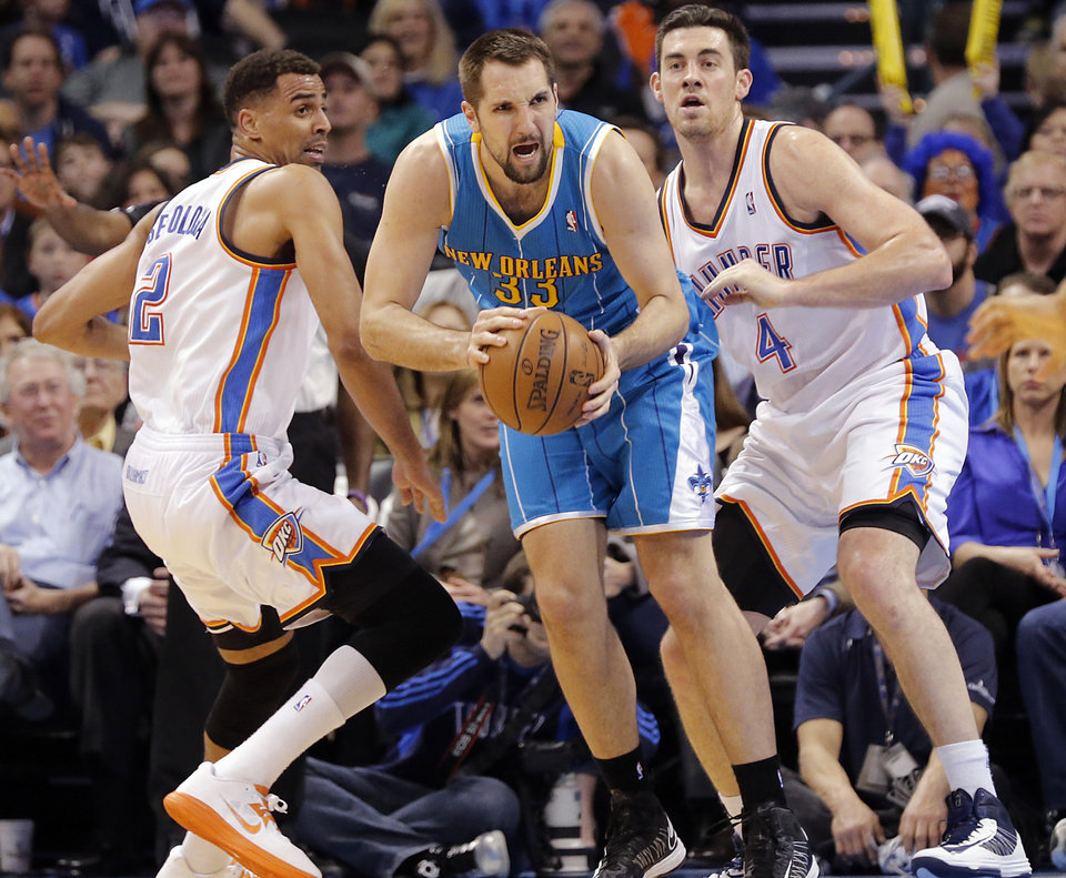Photo - Oklahoma City Thunder's Thabo Sefolosha (2) and Nick Collison (4) defend on New Orleans Hornets' Ryan Anderson (33) during the NBA basketball game between the Oklahoma City Thunder and the New Orleans Hornets at the Chesapeake Energy Arena on Wednesday, Feb. 27, 2013, in Oklahoma City, Okla. Photo by Chris Landsberger, The Oklahoman