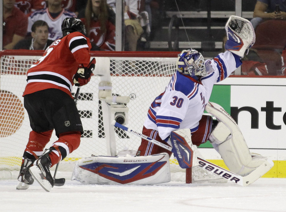 Photo -   New York Rangers goalie Henrik Lundqvist, right, of Sweden, stops a shot as New Jersey Devils right wing Dainius Zubrus, of Lithuania, looks for a rebound during the first period of Game 3 of the NHL hockey Stanley Cup Eastern Conference final playoff series, Saturday, May 19, 2012, in Newark, N.J. (AP Photo/Julio Cortez)