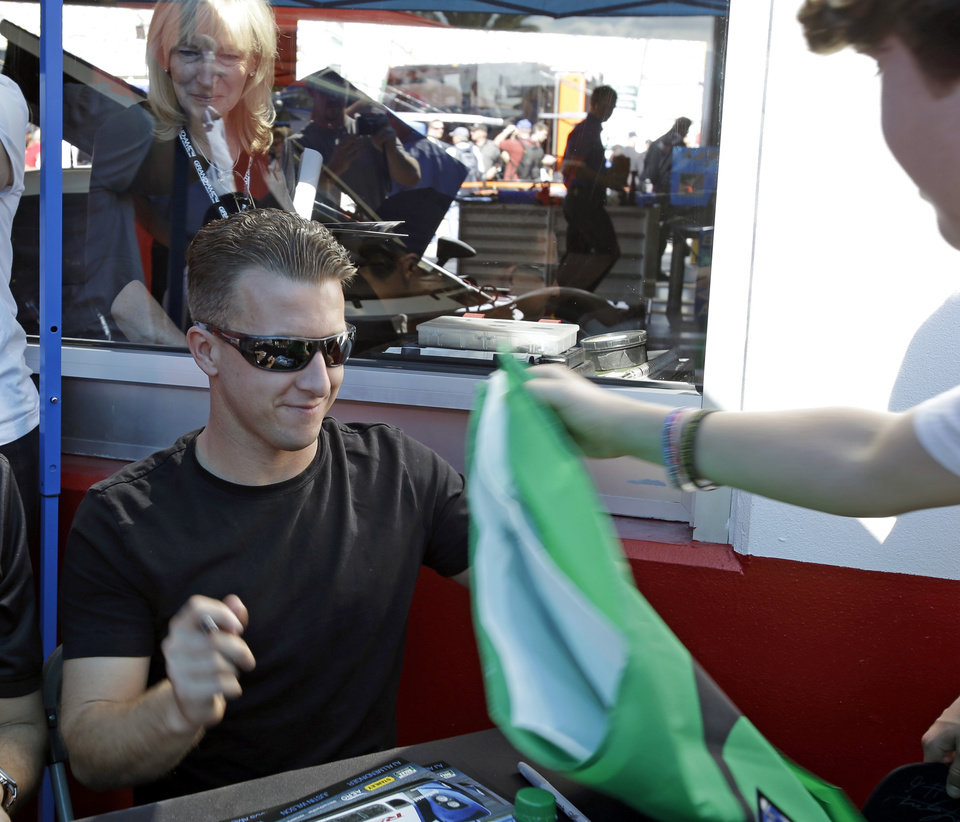 AJ Allmendinger signs autographs for fans before the Grand-Am Series Rolex 24 hour auto race at Daytona International Speedway, Saturday, Jan. 26, 2013, in Daytona Beach, Fla. (AP Photo/John Raoux)