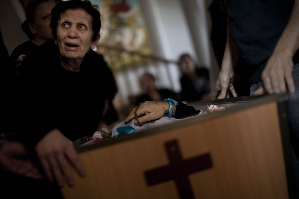 Photo -   A Palestinian mourner cries during the funeral of Salem Paul Sweliem in Gaza City, Tuesday, Nov. 20, 2012. According to the family, the 52 years old Greek Orthodox Christian carpenter was killed during an Israel Air Force strike on a high-rise building, in which Ramez Harb, a senior figure in Islamic Jihad's military wing, was killed. Sweliem was in car when the strike took place and he died on his way to the hospital from shrapnel wounds. (AP Photo/Bernat Armangue)