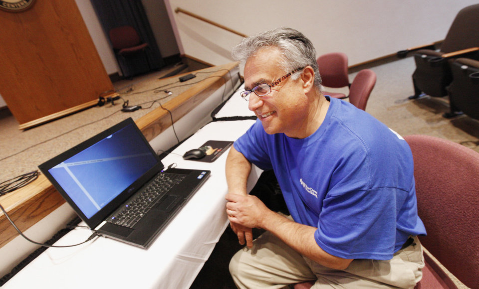 Photo - Matthew Ayadpoor, licensed insurance agent, sits in front of a laptop available for people to use to access the federal Health Insurance Marketplace at a training session Thursday sponsored by Blue Cross/Blue Shield of Oklahoma  in Oklahoma City. Photo by Paul B. Southerland, The Oklahoman  PAUL B. SOUTHERLAND