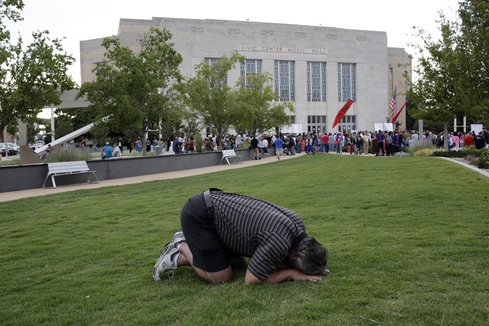 Photo - Christian Brim prays outside the Civic Center Music Hall where a Black Mass was taking place, Sunday, Sept. 21, 2014.  Photo by Garett Fisbeck, For The Oklahoman