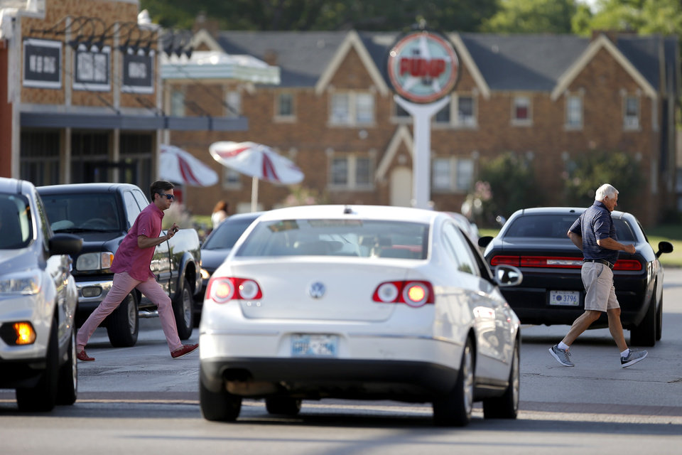 Photo -  People cross the street Tuesday along Walker Avenue just north of NW 23 in Oklahoma City. [Photo by Bryan Terry, The Oklahoman]