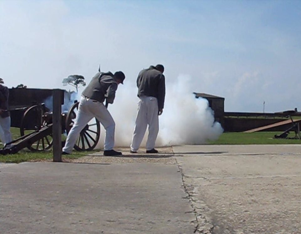 Photo - Volunteers in uniforms fire a cannon inside Fort Gaines, one of two forts at the mouth of Mobile Bay.