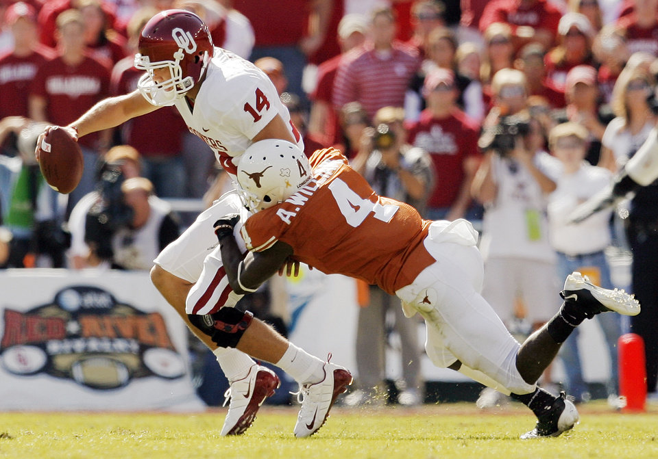 Photo - Aaron Williams (4) of Texas brings down OU quarterback Sam Bradford (14) in the first quarter during the Red River Rivalry college football game between the University of Oklahoma Sooners (OU) and the University of Texas Longhorns (UT) at the Cotton Bowl in Dallas, Texas, Saturday, Oct. 17, 2009. Bradford was injured on the play and did not return to the game. Photo by Nate Billings, The Oklahoman