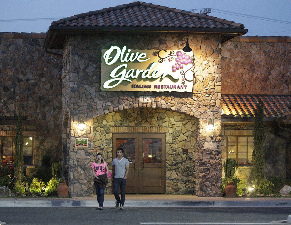Photo - In this May 22, 2014 photo, patrons exit an Olive Garden Restaurant, a Darden restaurant brand, in Short Pump, Va. Darden's fiscal fourth-quarter profit dropped 35 percent, dragged down by charges and costs tied to its strategic plan to reshape the restaurant company. (AP Photo/Steve Helber)