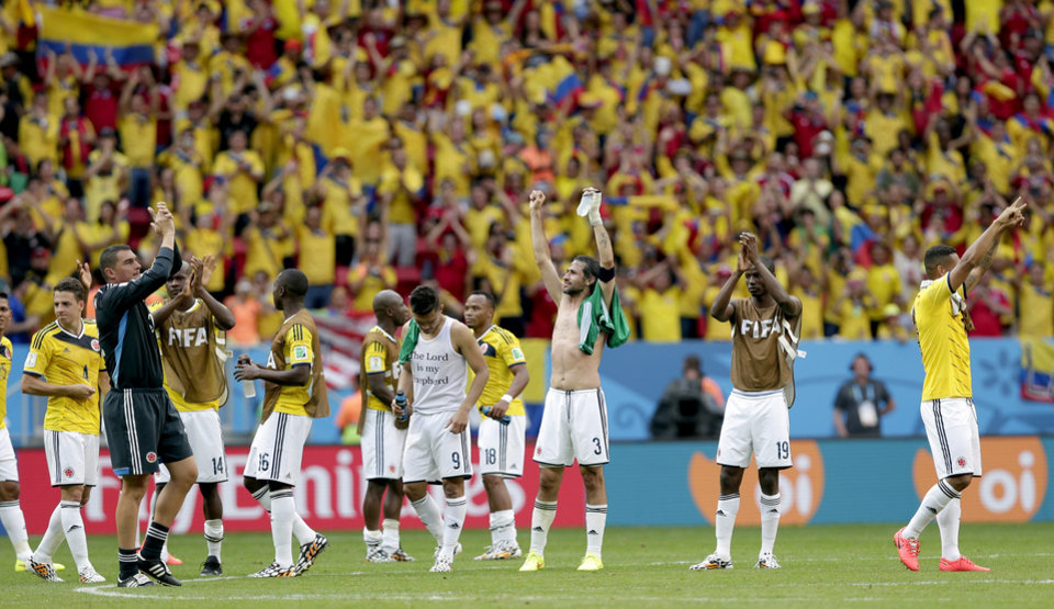 Photo - Colombian players celebrate after the group C World Cup soccer match between Colombia and Ivory Coast at the Estadio Nacional in Brasilia, Brazil, Thursday, June 19, 2014.  Colombia won the match 2-1.  (AP Photo/Marcio Jose Sanchez)