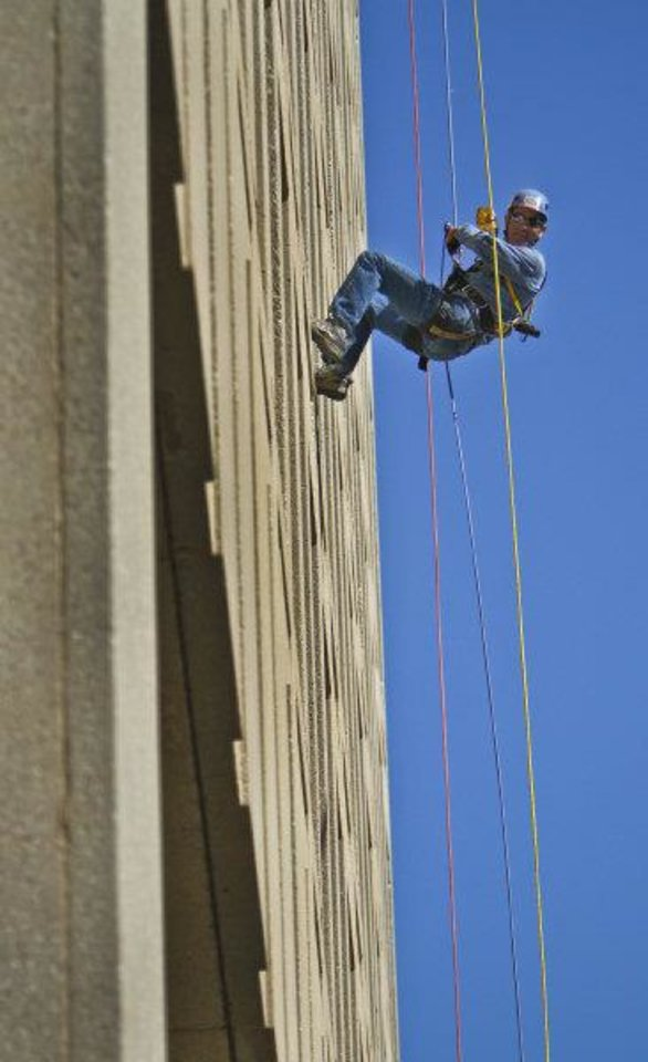 The Oklahoman reporter David Zizzo rappels down the Sandridge Building as part of a fundraising promotion to benefit Special Olympics Oklahoma. <strong>CHRIS LANDSBERGER - Chris Landsberger, The Oklahoman</strong>