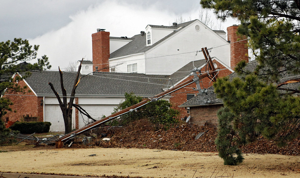 Photo - A power line lays on a house in the Oaktree addition after storms hit the area on Tuesday, Feb. 10, 2009, in Edmond, Okla.  PHOTO BY CHRIS LANDSBERGER, THE OKLAHOMAN
