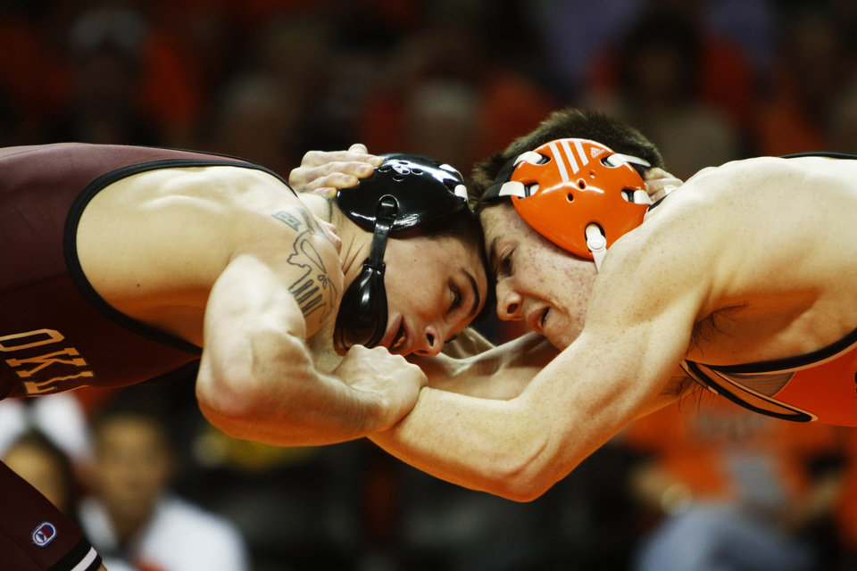 Photo - Oklahoma's 133-pound wrestler Cody Brewer and Oklahoma State's Jon Morrison grapple for position during a wrestling dual between Oklahoma State and Oklahoma at Gallagher Iba Arena in Stillwater on Feb. 9, 2014. Photo by KT King/For the Oklahoman