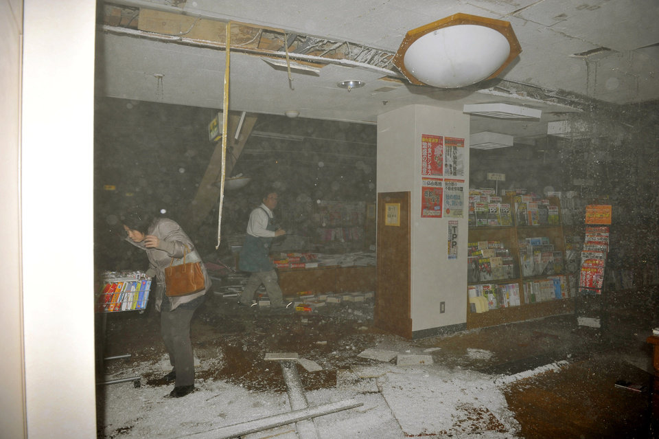 Photo - People at a book store react in Sendai, northern Japan as an earthquake hits Friday, March 11, 2011. Japan was struck by a magnitude-8.8 earthquake off its northeastern coast Friday, triggering a 13-foot (4-meter) tsunami that washed away cars and tore away buildings along the coast near the epicenter. (AP Photo/Kyodo News) JAPAN OUT, MANDATORY CREDIT, FOR COMMERCIAL USE ONLY IN NORTH AMERICA ORG XMIT: TOK804