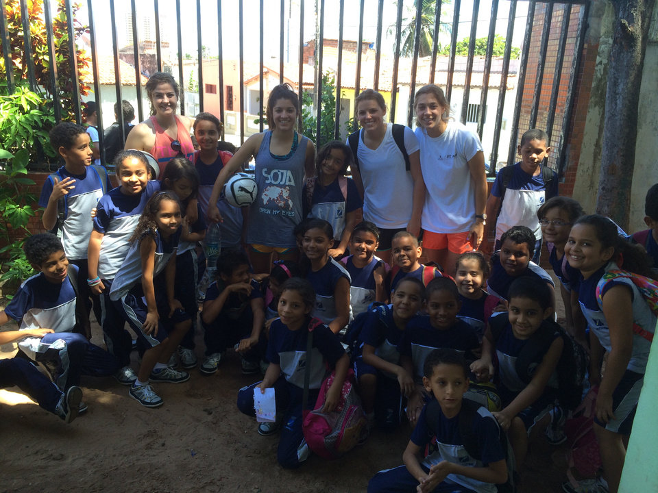 Photo -  Oklahoma Baptist University women's soccer team members seniors Allie Preston and Sarah Zeckser and sophomores Zoe Bauerschmidt and Morgan Knox pose for a picture with children attending a Brazilian school where the team presented the gospel message. Photo provided