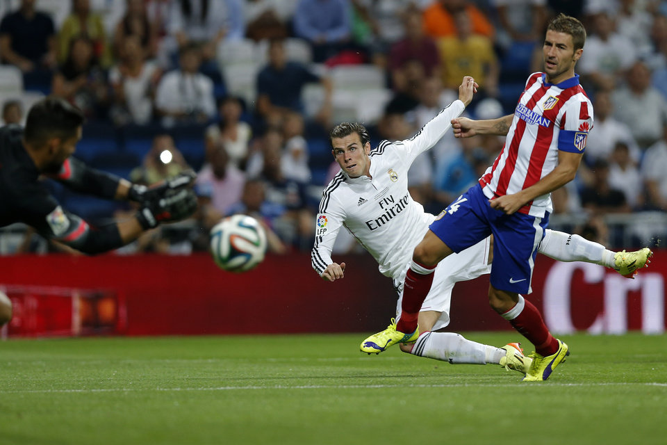 Photo - Real Madrid's Gareth Bale shot is saved by Atletico Madrid's goalkeeper Miguel Angel Moya, right, during a Spanish Super Cup soccer match at the Santiago Bernabeu stadium  in Madrid, Spain, Tuesday, Aug. 19, 2014. (AP Photo/Daniel Ochoa de Olza)