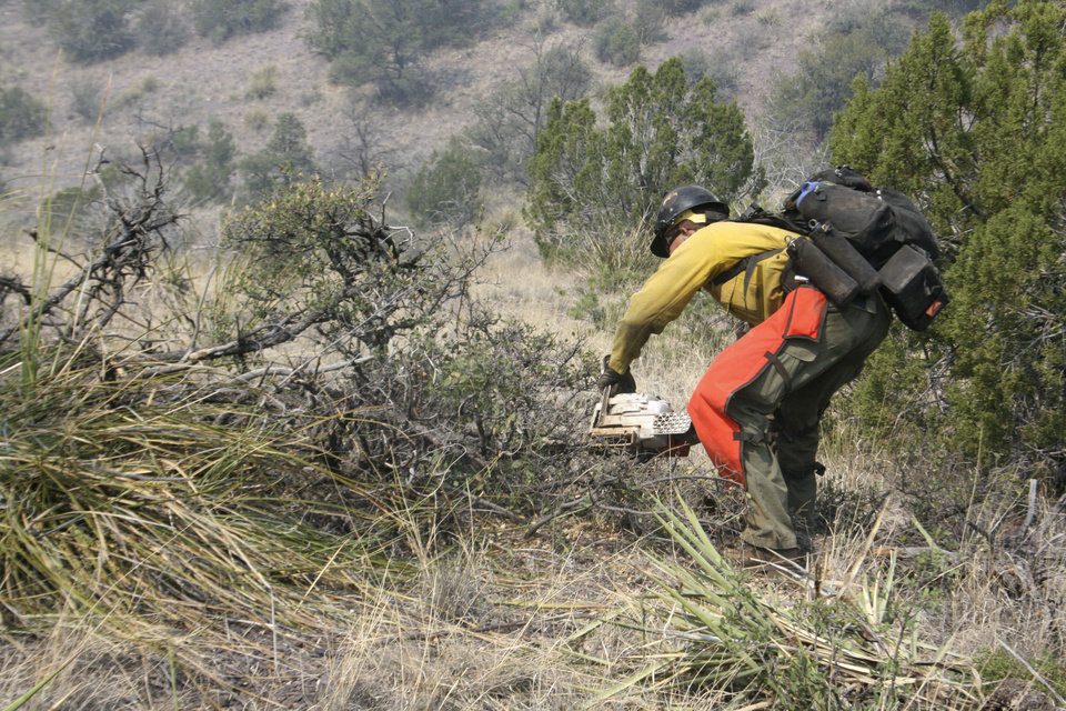 Photo -   A firefighter from the Granite Mountain Hotshots of Prescott, Ariz., clears brush along a ridge line outside Mogollon, New Mexico, Saturday, June 2, 2012, in an effort to manage and contain the Whitewater-Baldy fire which has burned more than 354 square miles of the Gila National Forest in New Mexico. Unlike last year's megafires in New Mexico and Arizona, this blaze is burning in territory that has been frequently blackened under the watchful eye of the Gila's fire managers. (AP Photo/U.S. Forest Service, Tara Ross)