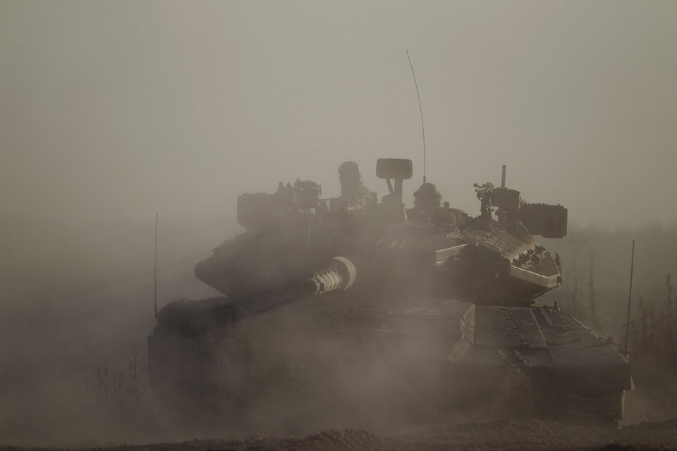 Photo - An Israeli tank takes a position along near the Israel-Gaza Border, Thursday, July 17, 2014. Israel and Hamas have begun observing a five-hour humanitarian cease-fire, as fighting extended into a 10th day. The two sides agreed to the pause following a request by the United Nations so that supplies could be delivered to Gaza.(AP Photo/Ariel Schalit)