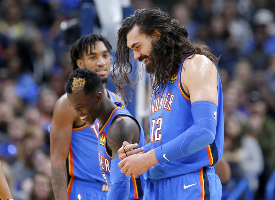Photo - Oklahoma City's Steven Adams (12) laughs with Dennis Schroder (17) after his pony tail fell out during the NBA game between the Oklahoma City Thunder and the Golden State Warriors at Chesapeake Energy Arena,   Saturday, Nov. 9, 2019.  [Sarah Phipps/The Oklahoman]