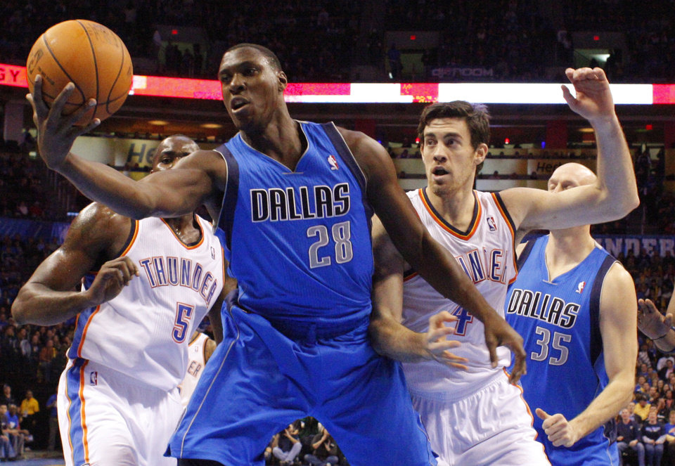 Photo - Dallas' Ian Mahinmi (28) goes for the ball in front of Oklahoma City's' Nick Collison (4) during a preseason NBA game between the Oklahoma City Thunder and the Dallas Mavericks at Chesapeake Energy Arena in Oklahoma City, Tuesday, Dec. 20, 2011. Photo by Bryan Terry, The Oklahoman