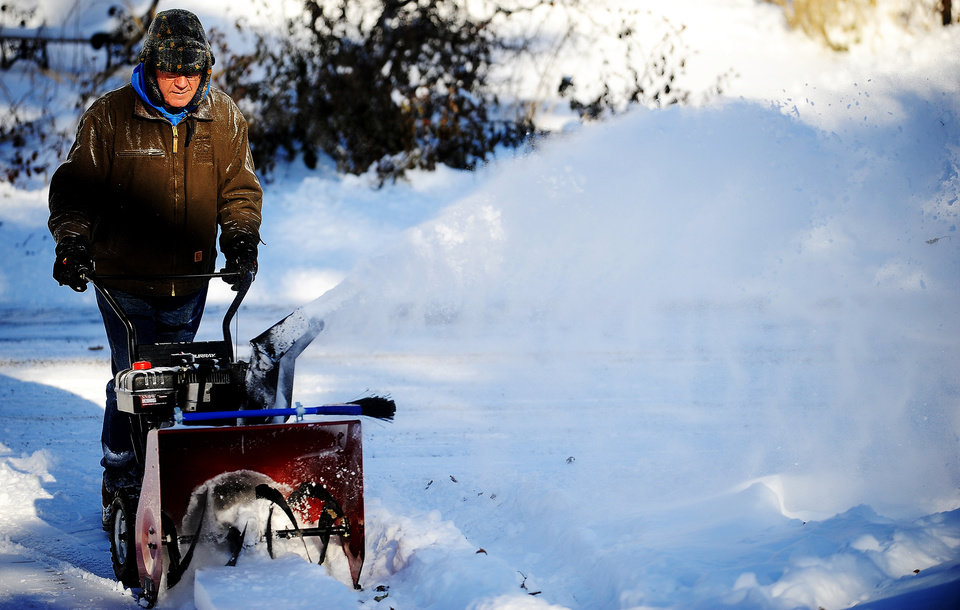 Photo - Bill Earley clears his driveway during Thursday's cold snap in Sioux Falls, S.D., on Thursday, Dec. 5, 2013. Winter storm and ice warnings are in effect through much of today for parts of six states in the Midwest. (AP Photo/Argus Leader, Joe Ahlquist)
