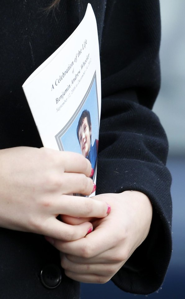 Photo - A woman carries a program with the photo of Andrew Wheeler, one of the students killed in the Sandy Hook Elementary School shooting last week, following his funeral services at Trinity Episcopal Church, Thursday, Dec. 20, 2012, in Newtown, Conn. Wheeler, 6, died when the gunman, Adam Lanza, walked into Sandy Hook Elementary School in Newtown, Conn., Dec. 14, and opened fire, killing 26 people, including 20 children, before killing himself. (AP Photo/Julio Cortez)