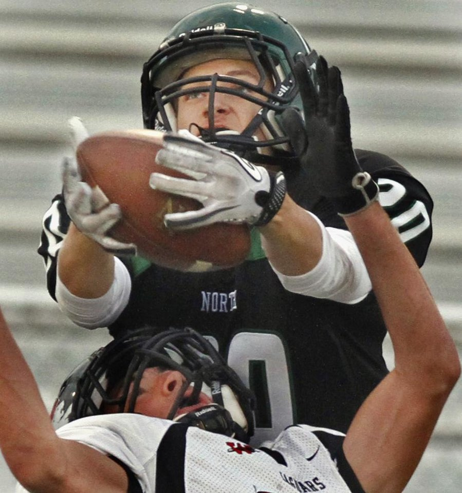 Norman North's Corbin Cleveland (20) catches a pass over defender Blake Martin (24) as the Norman North Timberwolves play the Westmoore Jaguars in high school football on Friday, September 16, 2011, in Norman, Okla.   Photo by Steve Sisney, The Oklahoman