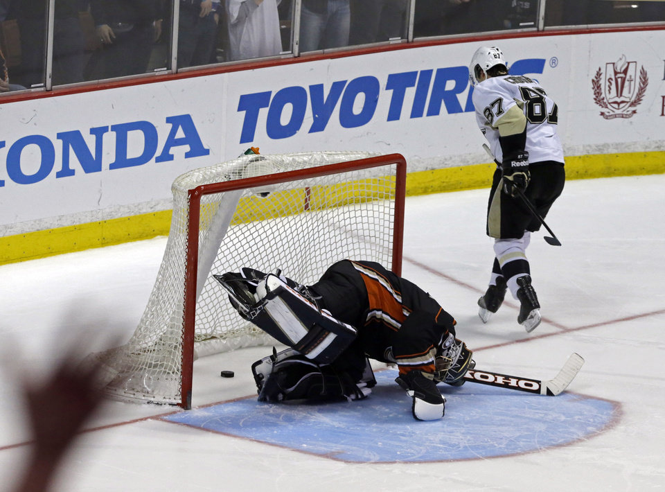 Photo - Anaheim Ducks goalie Jonas Hiller (1), of Switzerland, reacts after a goal by Pittsburgh Penguins center Sidney Crosby (87) in the third in s shootout in an NHL hockey game in Anaheim, Calif., Friday, March 7, 2014.  The Penguins won the shootout, 3-2. (AP Photo/Reed Saxon)