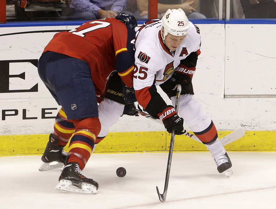 Photo - Florida Panthers defenseman Colby Robak (47) and Ottawa Senators right wing Chris Neil (25) battle for the puck during the second period of an NHL hockey game, Tuesday, March 25, 2014 in Sunrise, Fla. (AP Photo/Wilfredo Lee)