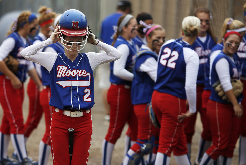 Moore's Caiti Hall (2) puts on her helmet before batting during the 6A state softball semifinals game between Moore and Broken Arrow at ASA Hall of Fame Stadium in Oklahoma City, Okla., Friday, Oct. 12, 2012.  Photo by Garett Fisbeck, The Oklahoman