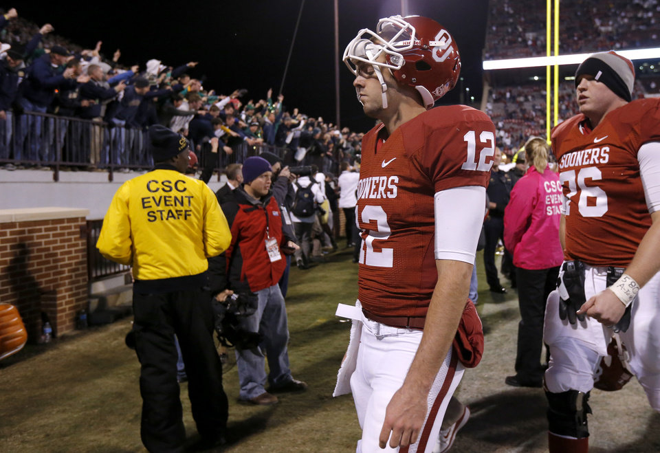 Photo - OU's Landry Jones (12) walks off the field as Notre Dame fans celebrate after the college football game between the University of Oklahoma Sooners (OU) and the Notre Dame Fighting Irish at Gaylord Family-Oklahoma Memorial Stadium in Norman, Okla., Saturday, Oct. 27, 2012. Oklahoma lost 30-13. Photo by Bryan Terry, The Oklahoman
